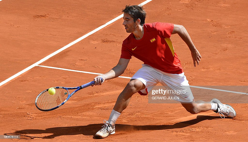 Spain's Marc Lopez returns the ball to Ukraine's Denys Molchanov during the Davis Cup World Group Play-offs 2013 at the Caja Magica sports complex in Madrid on September 15, 2013. Lopez won 6-3, 6-3.