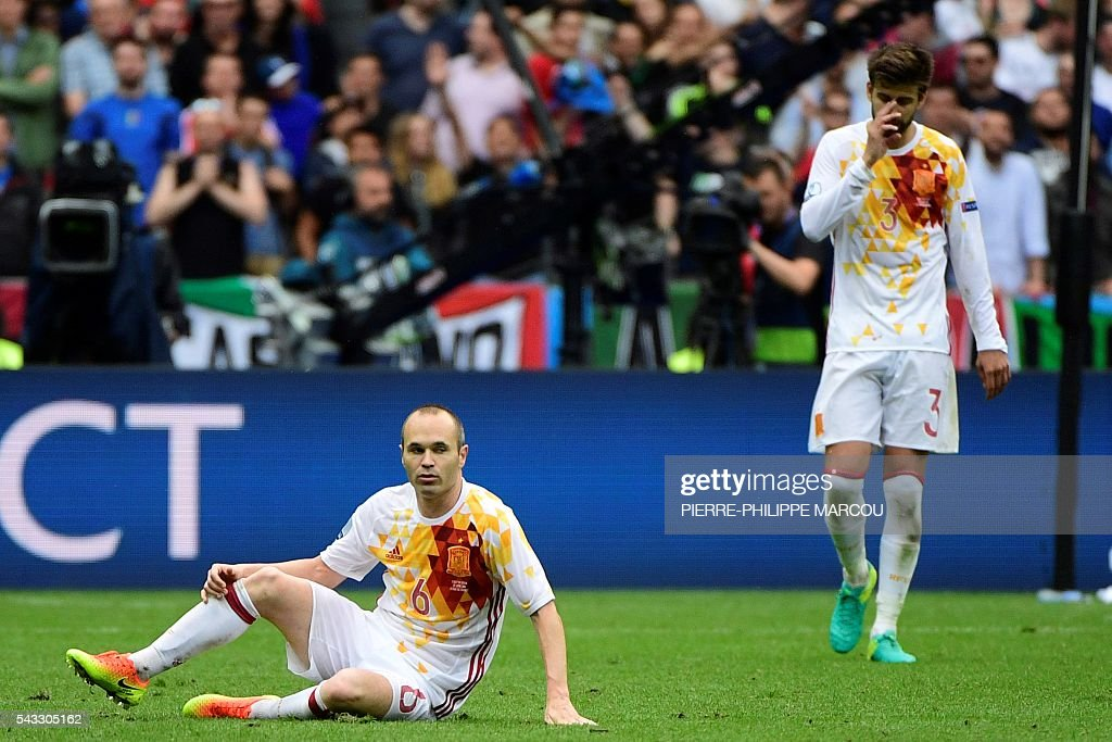 Spain's midfielder Andres Iniesta (L) and Spain's defender Gerard Pique react during Euro 2016 round of 16 football match between Italy and Spain at the Stade de France stadium in Saint-Denis, near Paris, on June 27, 2016. / AFP / PIERRE
