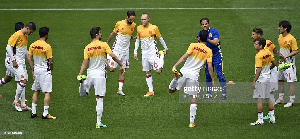 Spain's midfielder Andres Iniesta (C R) and Spain's defender Juanfran (C L) warm up with teammates before the Euro 2016 round of 16 football match between Italy and Spain at the Stade de France stadium in Saint-Denis, near Paris, on June 27, 2016. / AFP / PHILIPPE