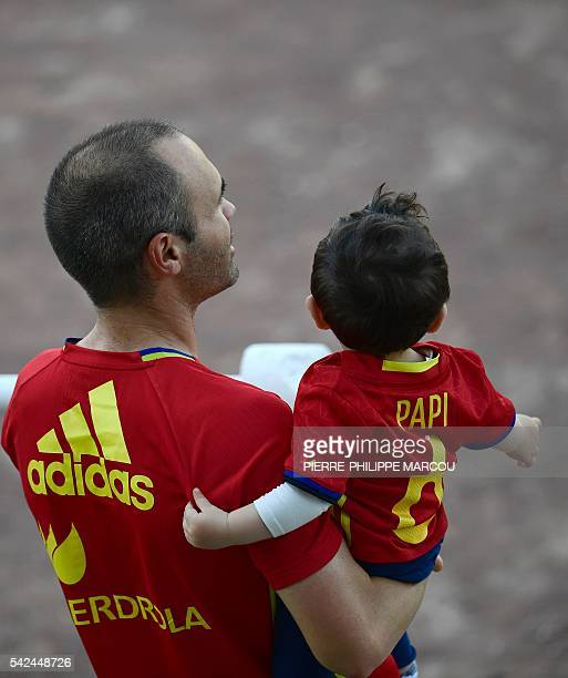 Spain's midfielder Andres Iniesta carries his son following a training session at Saint Martin de Re's stadium on June 23 2016 during the Euro 2016...