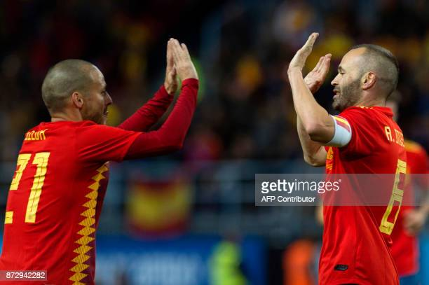 Spain's midfielder Andres Iniesta celebrates with midfielder David Silva after scoring during the international friendly football match Spain against...