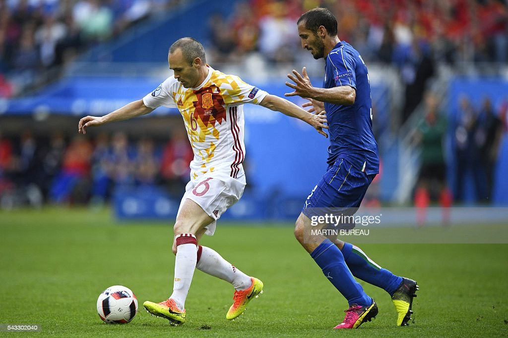 Spain's midfielder Andres Iniesta (L) vies for the ball against Italy's defender Giorgio Chiellini during Euro 2016 round of 16 football match between Italy and Spain at the Stade de France stadium in Saint-Denis, near Paris, on June 27, 2016. / AFP / MARTIN