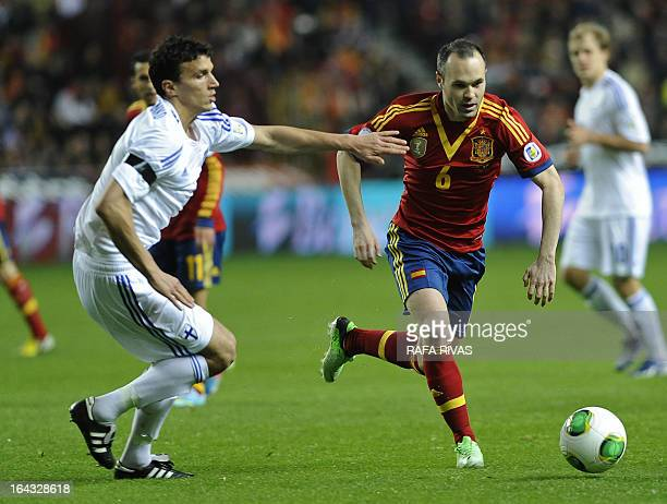 Spain's midfielder Andres Iniesta vies with Finland's midfielder Roman Eremenko during the FIFA 2014 World Cup qualifier football match Spain vs...