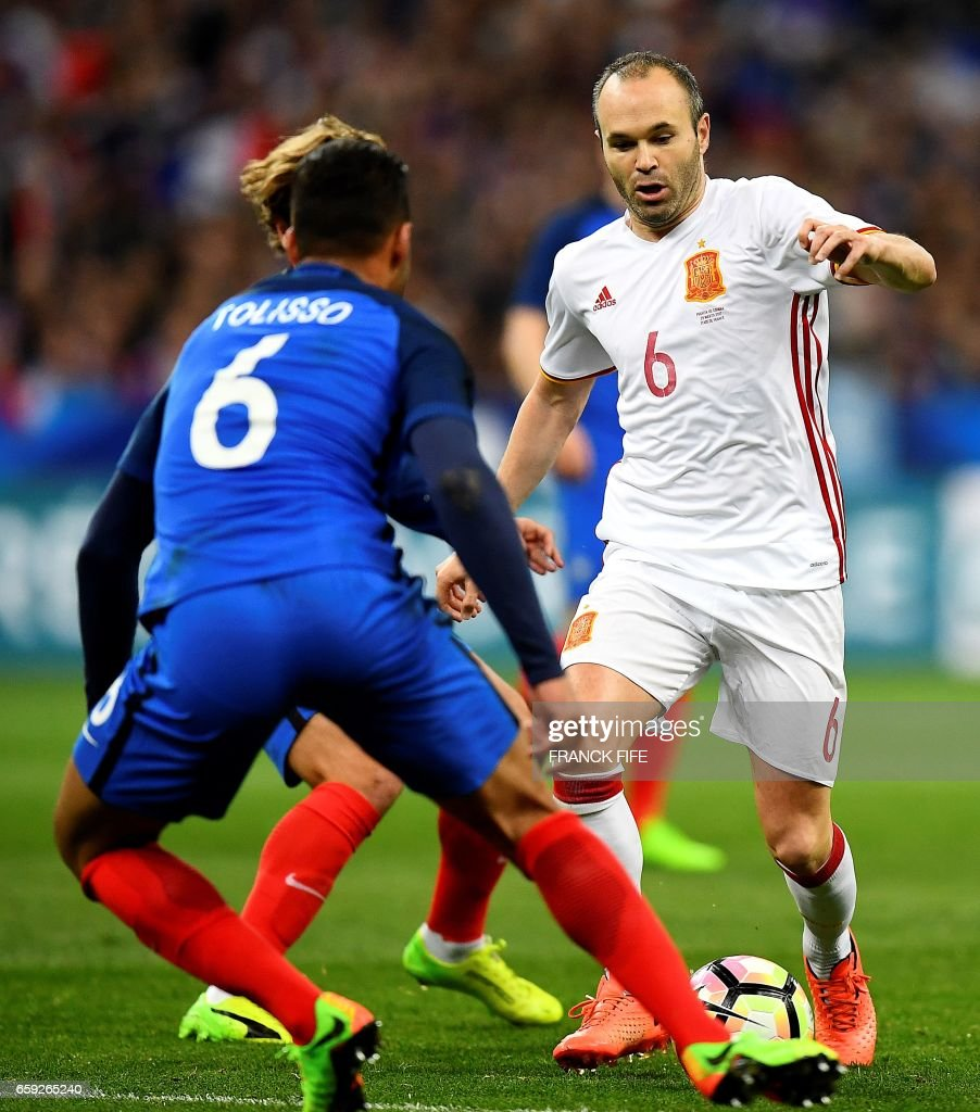 Spain s midfielder Andres Iniesta R vies with France s