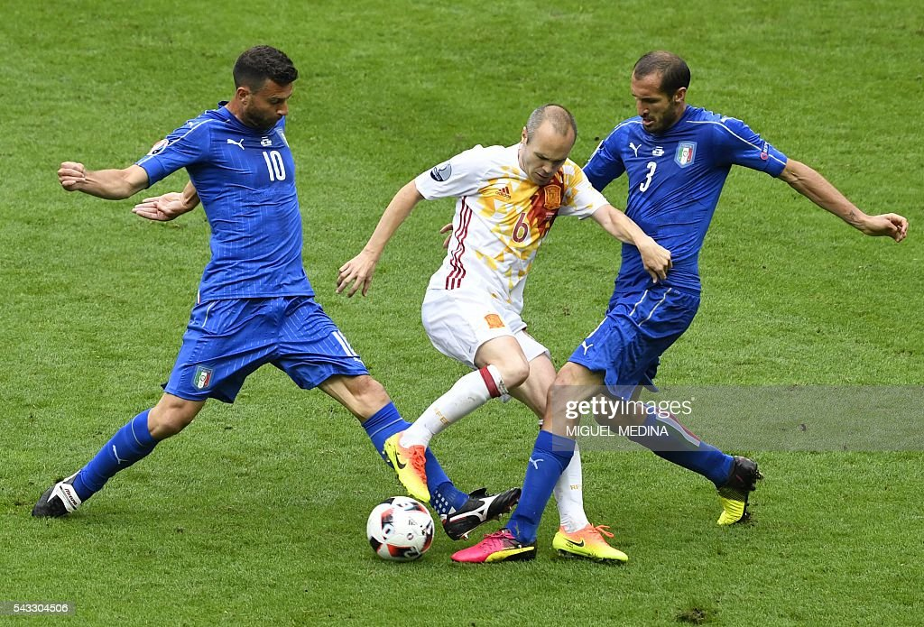 Spain's midfielder Andres Iniesta (C) vies with Italy's midfielder Thiago Motta (L) and Italy's defender Giorgio Chiellini during Euro 2016 round of 16 football match between Italy and Spain at the Stade de France stadium in Saint-Denis, near Paris, on June 27, 2016. / AFP / MIGUEL