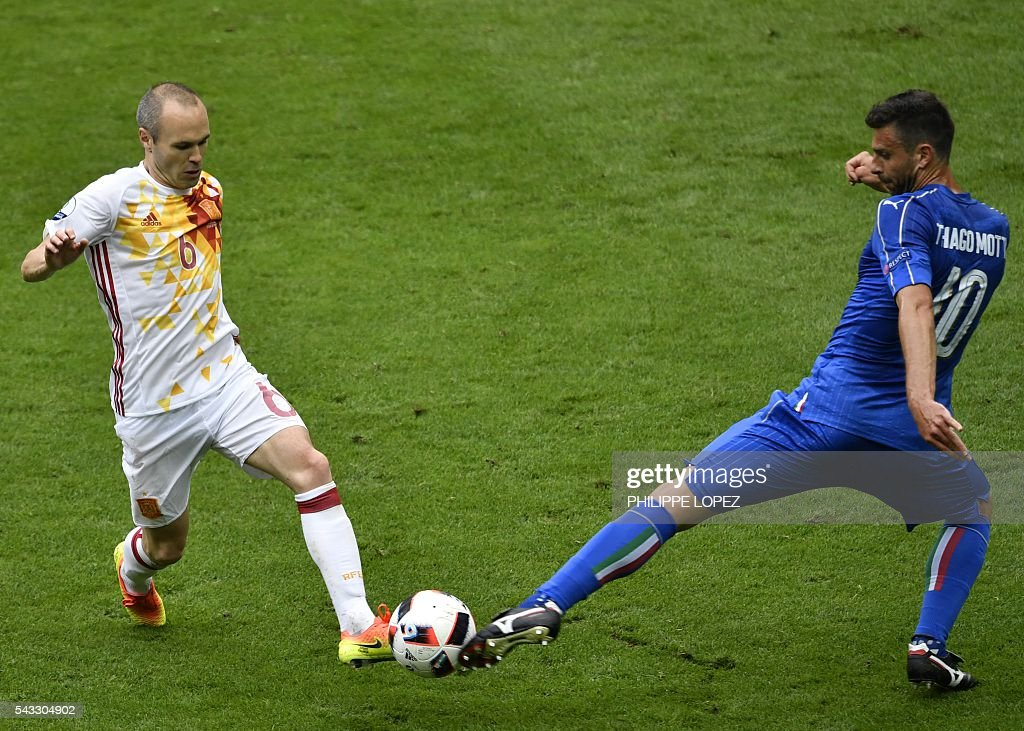 Spain's midfielder Andres Iniesta (L) vies with Italy's midfielder Thiago Motta during Euro 2016 round of 16 football match between Italy and Spain at the Stade de France stadium in Saint-Denis, near Paris, on June 27, 2016. / AFP / PHILIPPE