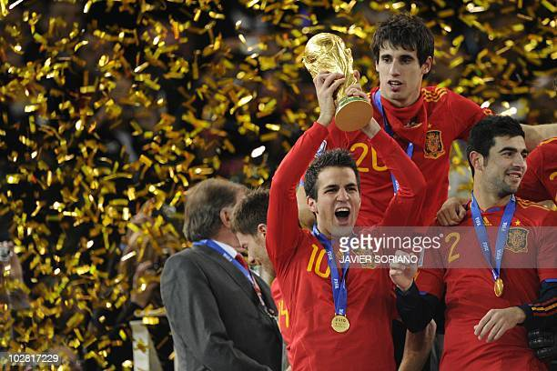 Spain's midfielder Cesc Fabregas holds the FIFA World Cup trophy after winning the 2010 World Cup football final by defeating The Netherlands during...