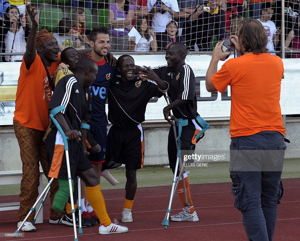 Spain's midfielder Cesc Fabregas (C) poses with Sierra Leone's war amputees football players before the training session of the Spanish football team on May 25, 2010, at the Sports City of Las Rozas, near Madrid. Spain, among the favourites for the World Cup, which runs from June 11-July 11, face Switzerland, Honduras and Chile in Group H of the opening round.