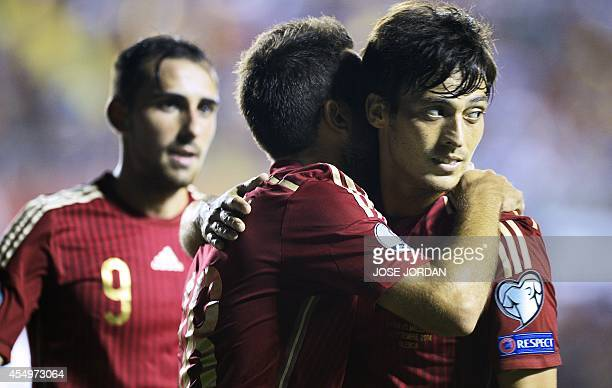Spain's midfielder David Silva celebrates with his teammates after scoring during the UEFA Euro 2016 group D qualifying football match Spain vs...