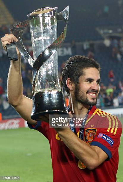 Spain's midfielder Isco celebrates with the trophy after beating Italy in their 2013 UEFA U21 Championship final football match at Teddy Stadium in...