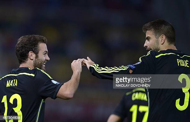 Spain's Midfielder Juan Mata celebrates with his teammate defender Gerard Pique after scoring during the Euro 2016 Group C qualifying football match...