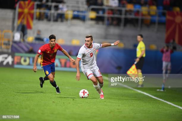 Spain's midfielder Marco Asensio and Macedonia's forward Marjan Radeski vie for the ball during the UEFA U21 European Championship Group B football...