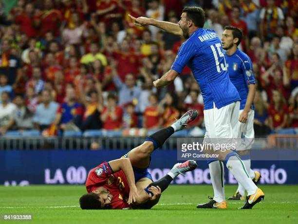 Spain's midfielder Marco Asensio lies on the field beside Italy's defender Andrea Barzagli during the World Cup 2018 qualifier football match between...
