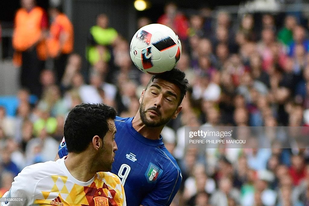 Spain's midfielder Sergio Busquets and Italy's forward Pelle vie for the ball during the Euro 2016 round of 16 football match between Italy and Spain at the Stade de France stadium in Saint-Denis, near Paris, on June 27, 2016. / AFP / PIERRE