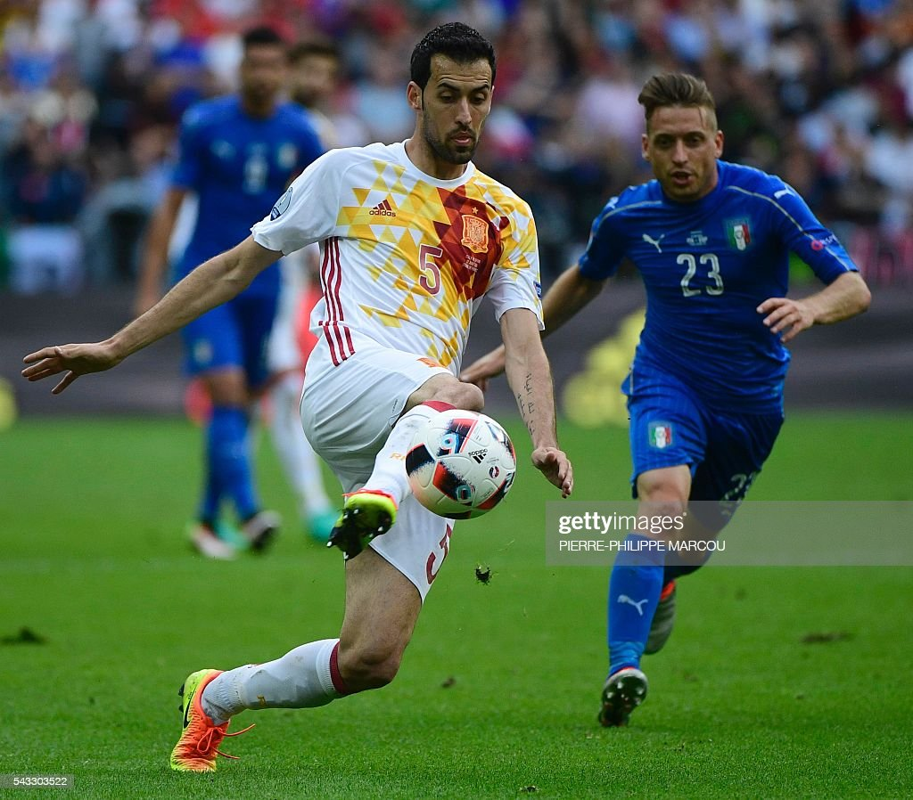 Spain's midfielder Sergio Busquets and Italy's midfielder Emanuele Giaccherini vie for the ball during the during the Euro 2016 round of 16 football match between Italy and Spain at the Stade de France stadium in Saint-Denis, near Paris, on June 27, 2016. / AFP / PIERRE