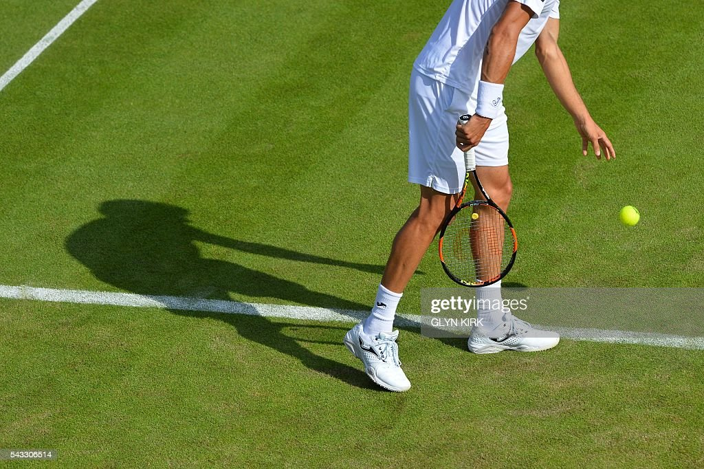 Spain's Pablo Carreno Busta prepares to serves against Canada's Milos Raonic during their men's singles first round match on the first day of the 2016 Wimbledon Championships at The All England Lawn Tennis Club in Wimbledon, southwest London, on June 27, 2016. / AFP / GLYN