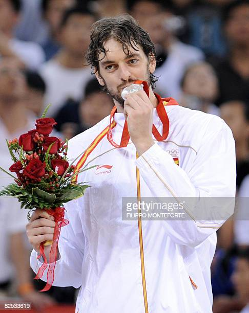 Spain's Pau Gasol bites his medal on the podium after the men's basketball gold medal match of the Beijing 2008 Olympic Games on August 24 2008 at...