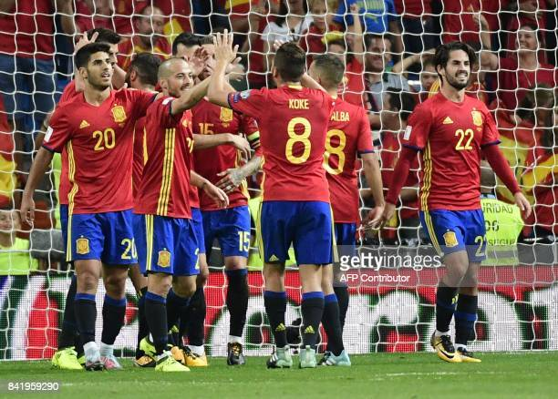 Spain's players celebrate their third goal during the World Cup 2018 qualifier football match between Spain and Italy at the Santiago Bernabeu...