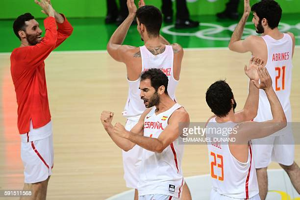Spain's point guard Jose Manuel Calderon and Spain's players celebrate after defeating France during a Men's quarterfinal basketball match between...