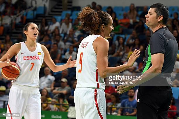 Spain's point guard Laia Palau and Spain's forward Alba Torrens talk to Australia's umpire Scott Beker during a Women's semifinal basketball match...