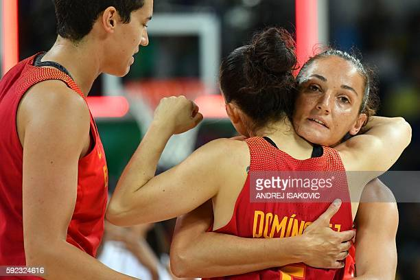 Spain's point guard Laia Palau embraces Spain's point guard Silvia Dominguez as Spain's power forward Laura Nicholls looks on after losing to USA...