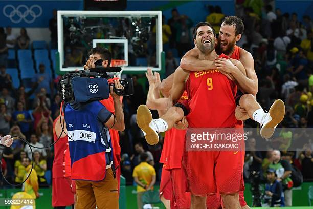 Spain's power forward Felipe Reyes carries Spain's point guard Sergio Rodriguez as Spain's players celebrate after defeating Australia during a Men's...