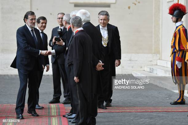 Spain's Prime Minister Mariano Rajoy Brey is welcomed by the prefect of the papal household Georg Gaenswein as he arrives for an audience of Pope...