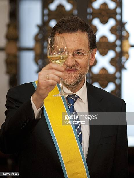Spain's Prime Minister Mariano Rajoy drinks a toast with Mexican President Felipe Calderon after being decorated with the 'Order of The Azteca Eagle...