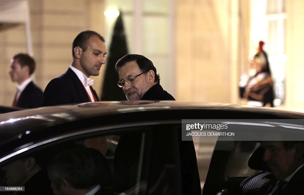 Spain's Prime Minister Mariano Rajoy (C) gets into a car as he leaves the Elysee presidential Palace following a meeting with France's President on March 26, 2013, to attend the World Cup 2014 qualifying football match France vs Spain at the Stade de France in Saint-Denis, north of Paris. AFP PHOTO / JACQUES DEMARTHON