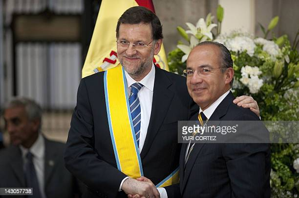 Spain's Prime Minister Mariano Rajoy shakes hands with Mexican President Felipe Calderon after he received the 'Decoration of the Order of The Azteca...