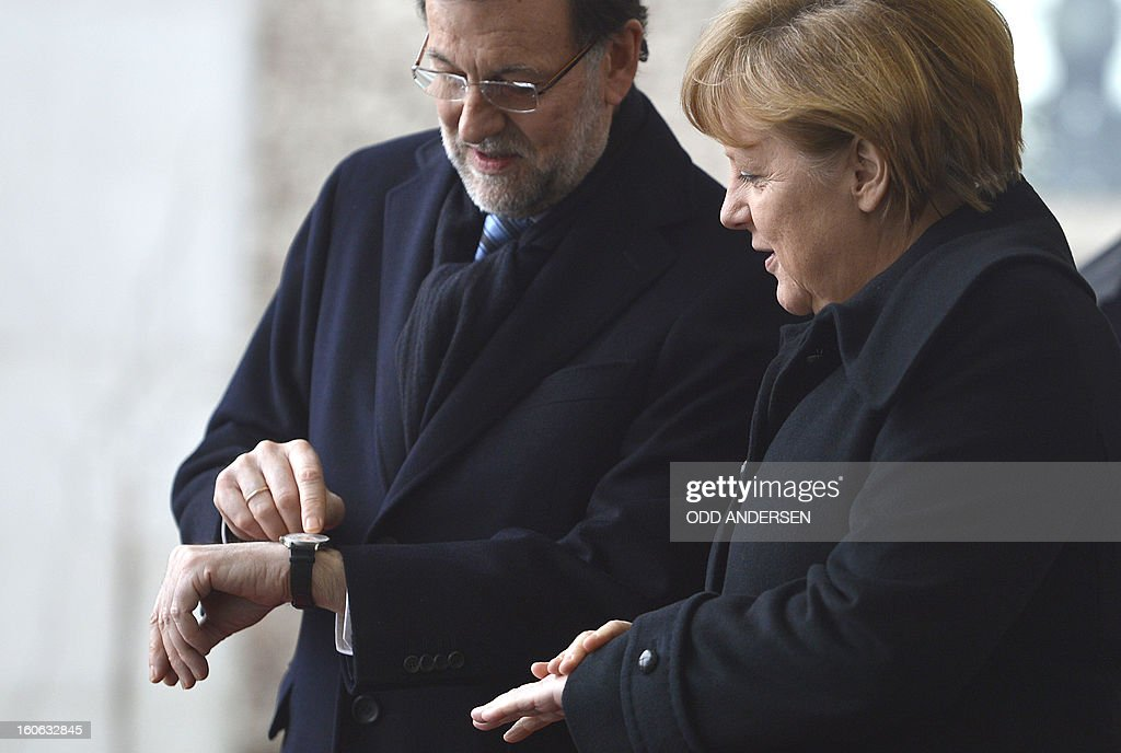Spain's prime minister Mariano Rajoy (L) shows his arm-clock as he is greeted by German Chancellor Angela Merkel (R) upon his arrival at the Chancellery in Berlin on February 4, 2013 before their meeting. Merkel hosts for talks Rajoy, currently under fire for alleged corruption.