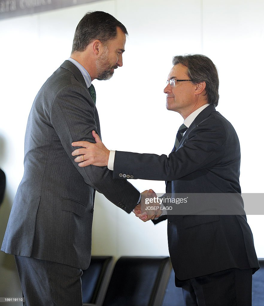Spain's Prince Felipe (L) shakes hands to President of the Catalonia regional government and leader of the Catalan party CIU (Convergence and Unity party) Artur Mas, prior to getting onboard a train at Sants, Barcelona's train station, during the inauguration of the high-speed line between Barcelona and the french border, on January 8, 2013.