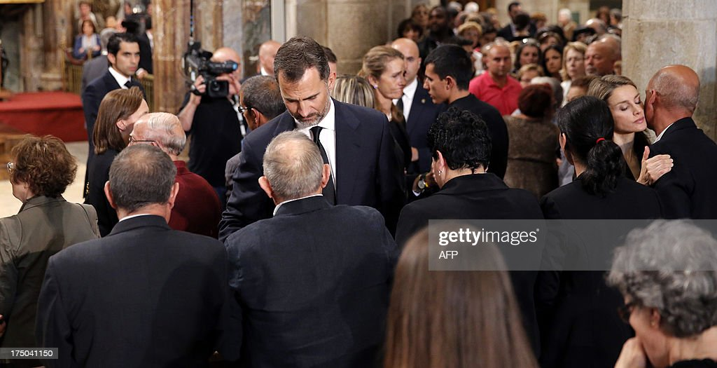 Spain's Princess Letizia (R) and Spain's Crown Prince Felipe (R) comfort relatives of the victims after a memorial service for the victims the derailed train of Angrois, at the cathedral of Santiago de Compostela on July 29, 2013. The driver of a train that hurtled off the rails in Spain was charged on July 28 with 79 counts of reckless homicide and released on bail after being questioned by a judge.
