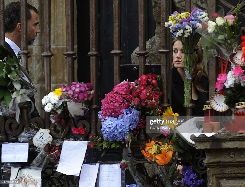 Spain's Princess Letizia (R) and Spain's Crown Prince Felipe walk past flowers and candles displayed at the Obradoiro Square as they arrive to attend a memorial service for the victims the derailed train of Angrois, at the cathedral of Santiago de Compostela on July 29, 2013. The driver of a train that hurtled off the rails in Spain was charged on July 28 with 79 counts of reckless homicide and released on bail after being questioned by a judge.