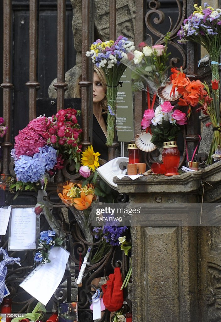 Spain's Princess Letizia looks at flowers and candles displayed at the Obradoiro Square as she arrives to attend a memorial service for the victims the derailed train of Angrois, at the cathedral of Santiago de Compostela on July 29, 2013. The driver of a train that hurtled off the rails in Spain was charged on July 28 with 79 counts of reckless homicide and released on bail after being questioned by a judge.