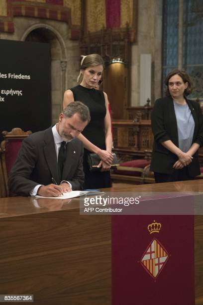 Spain's Queen Letizia and Barcelona's mayor Ada Colau stand next to Spanish king Felipe VI signing the condolences book for the victims of the...