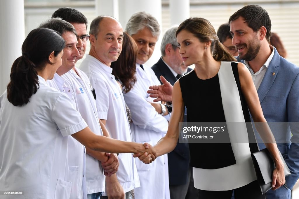 Spain's Queen Letizia (2nd R) shakes hands with medical staff as she arrives at the Hospital del Mar in Barcelona to visit victims of the Barcelona attack on August 19, 2017, two day after a van ploughed into the crowd, killing 13 persons and injuring over 100. Drivers have ploughed on August 17, 2017 into pedestrians in two quick-succession, separate attacks in Barcelona and another popular Spanish seaside city, leaving 14 people dead and injuring more than 100 others. / AFP PHOTO / Pascal GUYOT