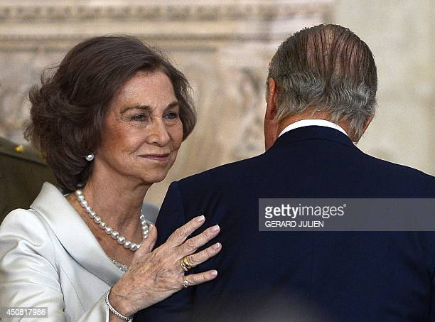 Spain's Queen Sofia touches Spain's King Juan Carlos during the ceremony of approval and enactment of a law bringing into effect King Juan Carlo's...
