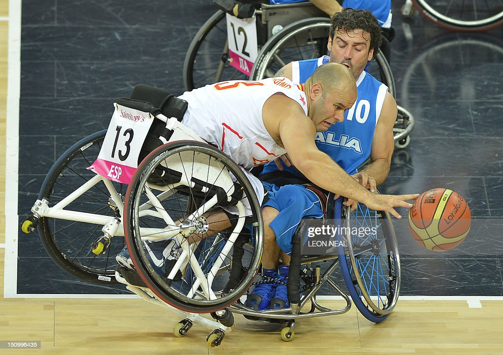 Spain's Rafael Muino Gamez (L) collides with Italy's Damiano Airoldi (R) during their preliminary men's group A wheelchair basketball match during the London 2012 Paralympic Games at the North Greenwich Arena in London on August 30, 2012. AFP PHOTO / LEON NEAL