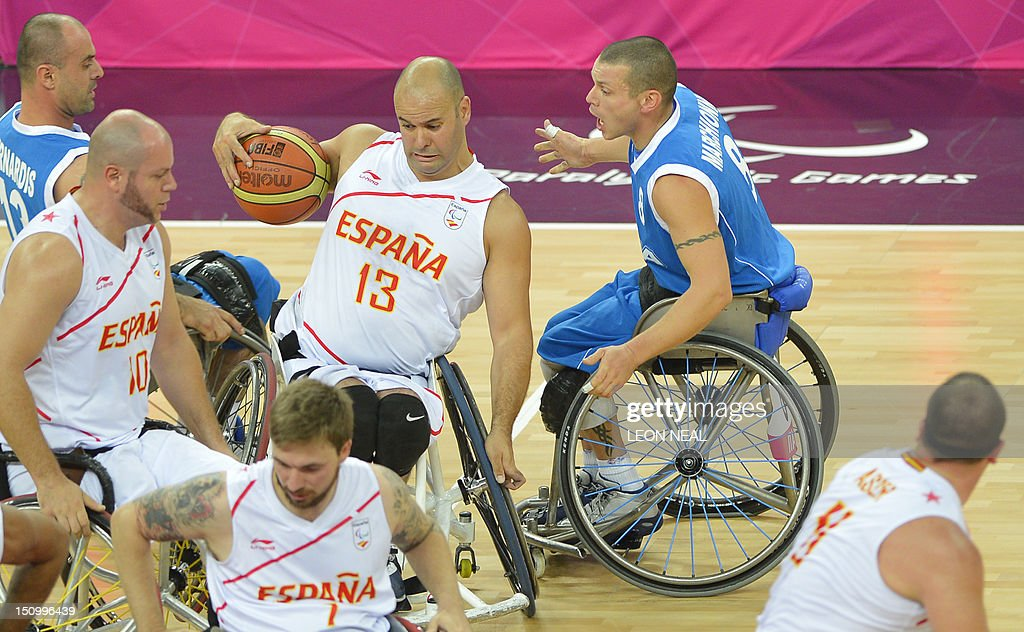Spain's Rafael Muino Gamez (C) evades Italy's Galliano Marchionni (R) during their preliminary men's group A wheelchair basketball match during the London 2012 Paralympic Games at the North Greenwich Arena in London on August 30, 2012.