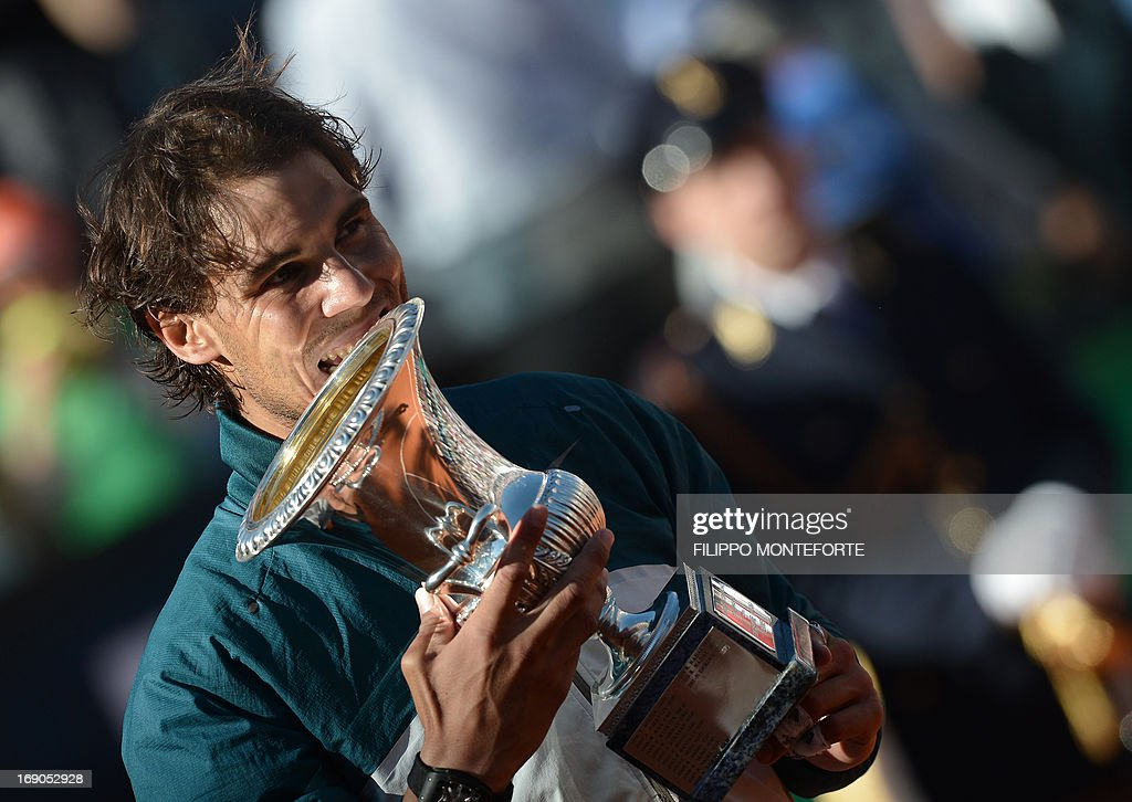 Spain's Rafael Nadal bites the cup during the trophy ceremony of the ATP Rome Masters on May 19, 2013. Nadal crushes Switzerland's Roger Federer 6-1, 6-3 to win seventh Rome title.