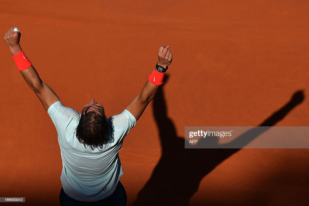 Spain's Rafael Nadal celebrates defeating Switzerland's Roger Federer at the end of the final of the ATP Rome Masters on May 19, 2013. Nadal crushes Federer 6-1, 6-3 to win seventh Rome title. AFP PHOTO / GABRIEL BOUYS