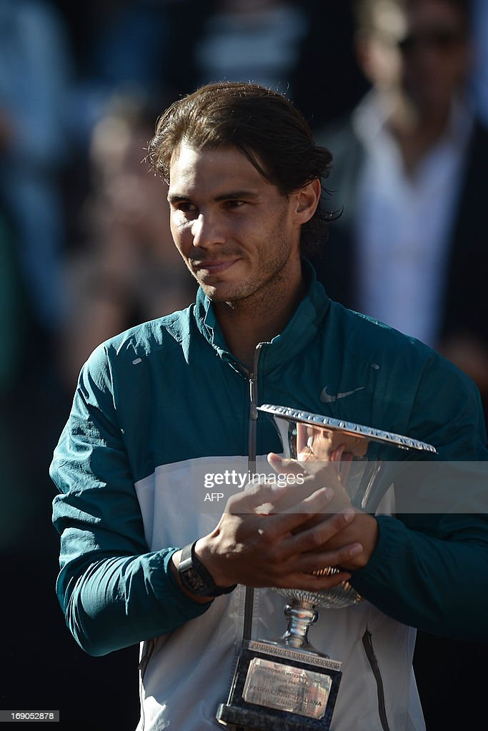 Spain's Rafael Nadal celebrates with the trophy during the ceremony of the ATP Rome Masters on May 19, 2013. Nadal crushes Switzerland's Roger Federer 6-1, 6-3 to win seventh Rome title. AFP PHOTO / FILIPPO MONTEFORTE