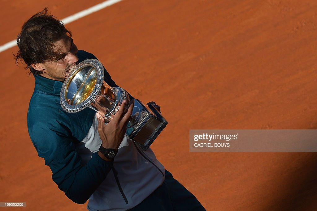 Spain's Rafael Nadal celebrates with the trophy during the ceremony of the ATP Rome Masters on May 19, 2013. Nadal crushes Switzerland's Roger Federer 6-1, 6-3 to win seventh Rome title. AFP PHOTO / GABRIEL BOUYS