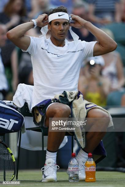 Spain's Rafael Nadal chages his head band during a break in play against US player Donald Young during their men's singles second round match on the...