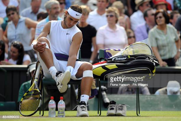 Spain's Rafael Nadal changes his trainers during the Wimbledon Championships 2008 at the All England Tennis Club in Wimbledon