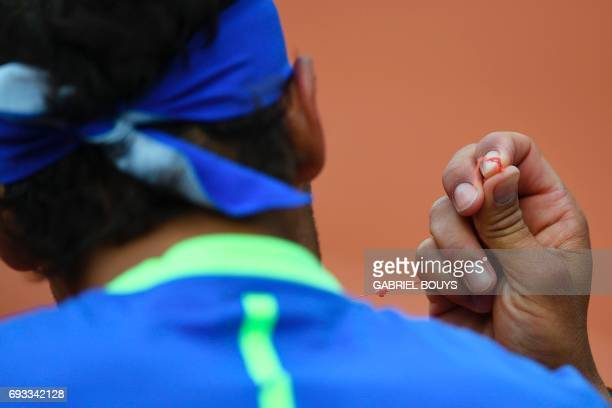 Spain's Rafael Nadal fixes a thread as he plays against Spain's Pablo Carreno Busta during their tennis match at the Roland Garros 2017 French Open...