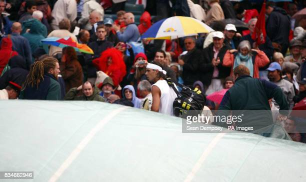 Spain's Rafael Nadal leaves Centre Court as rain delays play and the covers are brought on during the Wimbledon Championships 2008 at the All England...