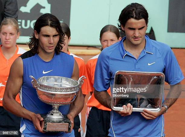 Spain's Rafael Nadal left and Switzerland's Roger Federer are seen holding their trophies after Nadal's win at the men's final of the French Open...