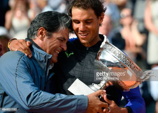 Spain's Rafael Nadal poses with his trophy with his uncle and former Spanish tennis player Toni Nadal after winning the men's final tennis match...
